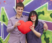 Teens with heart near graffiti wall. — Stock Photo