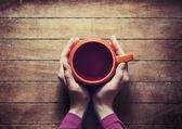 Femme tenant la tasse de thé chaud — Photo