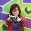 Style teen girl with camera standing near graffiti wall — Stock Photo