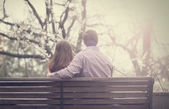 Young couple on the bench at the street. — Stock Photo