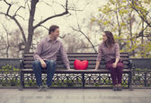 Happy teens sitting at the bench at alley at the park — ストック写真