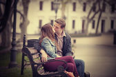 Couple kissing at the bench at alley. — Stock Photo