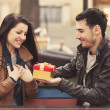 The young man gives a gift to a young girl in the cafe and they — Stock Photo #24553999