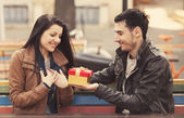 The young man gives a gift to a young girl in the cafe and they — Stock Photo