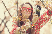 Teen girl in glasses with vintage camera near blossom tree — Stock Photo