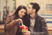 O jovem dá um presente para uma jovem num café e eles — Foto Stock