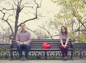 Sad teens sitting at the bench at the park — Stok fotoğraf