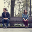 Stock Photo: Sad teens sitting at the bench at the park