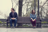 Sad teens sitting at the bench at the park — 图库照片