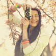 Beautiful girl with camera in spring park — Stock Photo