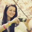Beautiful girl with camera in spring park — Stock Photo #24607663