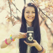 Beautiful girl with camera in spring park — Stock Photo #24607675