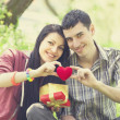 Couple with gift at green grass — Stock Photo