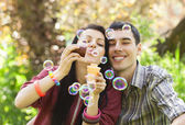 Couple Relaxing in the Park with bubble blower — Stock Photo