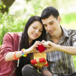 Couple with gift at green grass in the park — Stock Photo
