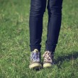 Girl in vintage sneakers resting on the grass — Stock Photo