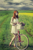 Girl on a bike in the countryside — Stock Photo