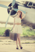 Lonely girl with suitcase at near airplane. — Stock Photo