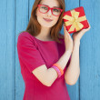Redhead girl in glasses with gift near wood background — Stok fotoğraf