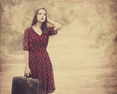 Redhead girl with suitcase at tree's alley. — Stock Photo