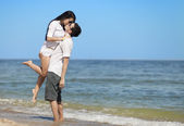 Beautiful couple kissing on the beach. — Stock Photo