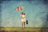 Redhead enchantress with umbrella and suitcase at spring country — Stock Photo