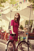Redhead girl with bike at outdoor, city. — Stock Photo
