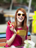 Style redhead girl with gift sitting on the bench in the cafe — Stock Photo