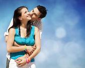 Hermosa pareja besándose sobre fondo de cielo azul — Foto de Stock