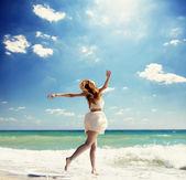 Küçük kızıl saçlı kız plajda atlama. — Stok fotoğraf