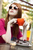 Style redhead girl with cup and cake — Stock Photo