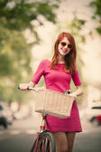 Redhead girl with bike on the street — Stock Photo