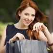 Style redhead women sitting on the bench with shopping bags — Stock Photo