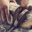 Male hands slicing home-made bread — Stock Photo #25841259
