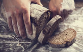 Male hands slicing home-made bread — Stock Photo