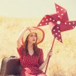Redhead girl with suitcase and wind turbine sitting at grass — Stock Photo #26089761