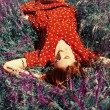 Girl lying on spring grass and flowers. — Stock Photo