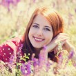 Redhead girl at green grass at village outdoor — Stock Photo #26089927