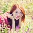 Redhead girl at green grass at village outdoor — Stock Photo #26089945