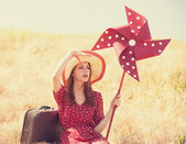 Redhead girl with suitcase and wind turbine sitting at grass — Stock Photo