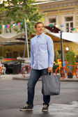 Man with shopping bags walking outdoors — Stock Photo