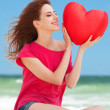 Redhead teen girl with heart shape on the beach — Stock Photo