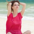 Funny teen girl sitting on the sand at the beach. — Stock Photo #26090087