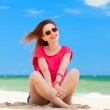 Funny teen girl sitting on the sand at the beach. — Stock Photo #26090097