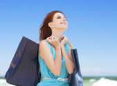 Redhead teen girl with shopping bags on the beach — Stock Photo