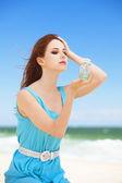 Redhead girl with perfume on the beach — Stock Photo