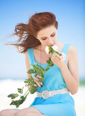 Redhead teen girl with rose on the beach — Stock Photo