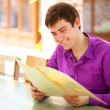 Young man sitting in the cafe and looking in the menu. — Stock Photo