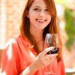 Redhead girl with glass of wine in the cafe — Stock Photo