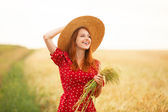 Redhead girl in red dress at wheat field — Stock Photo